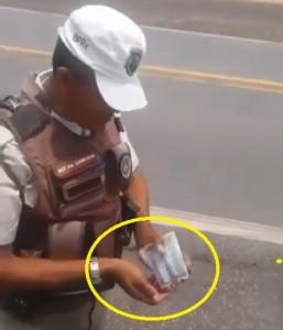 sargento da Polícia Rodoviária pega dinheiro em carteira de caminhoneiro